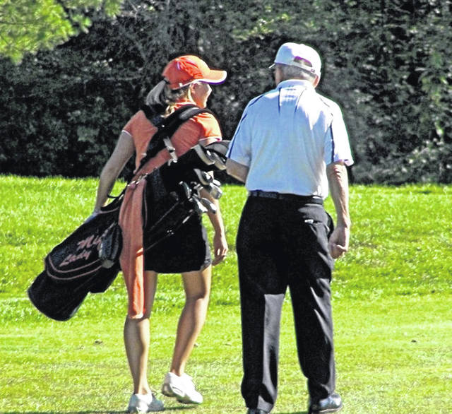 Don Seyfried talks with a member of the Minster girls golf team.