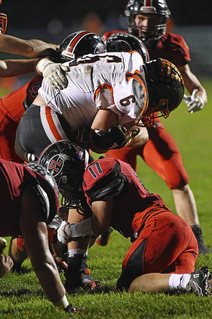 Fort Loramie defenders tackle an Ansonia player during a Division VII, Region 28 quarterfinal on Friday at Redskin Stadium in Fort Loramie. The Redskins won 42-0.