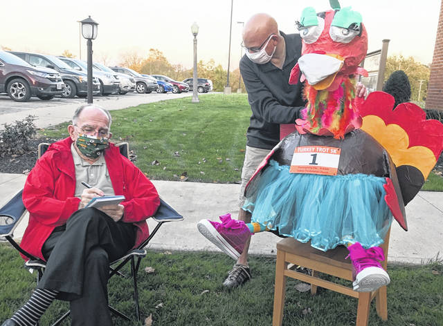 Darryl Cloud, left, and Eric Thomas, right, both members of First Presbyterian Church as well as the Turkey Trot Planning Committee, talk with Tootie the Traveling Tutu'd Turkey about plans for this year's event. Instead of a 5K walk/run, different activities have been planed due to COVID-19.