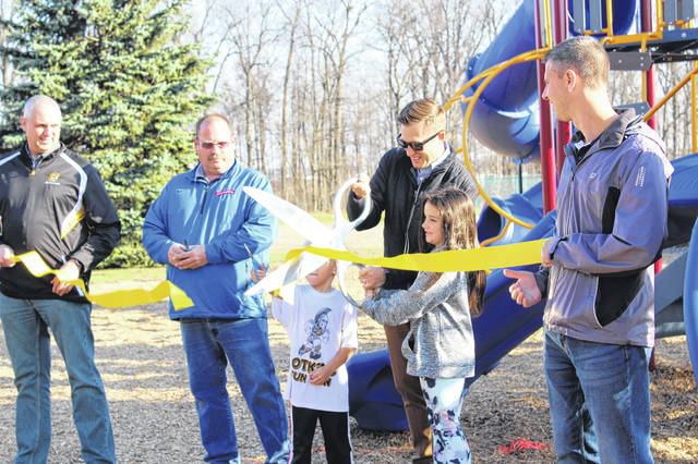 Hailey Schwind, 9, second from right, daughter of Kristie Schwind and Jeff Spencer, helps Botkins Village Council member Lance Symonds cut the ribbon at Botkins Community Park on Friday, Nov. 20. The park is located off of Ohio 219 and includes a playground, two soccer fields, a baseball field, a softball field, a track and a basketball court.