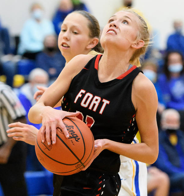 Fort Loramie senior guard Caitlyn Gasson shoots with pressure from Russia's Sophie Francis during the second half of a Shelby County Athletic League game on Tuesday at Clair C. Naveau Gymnasium in Russia. Gasson scored eight points.
