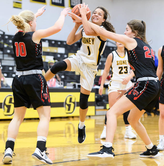 Sidney freshman Kiara Hudgins shoots with pressure from Tippecanoe's Maddi Moran, left, and Ashley Aselage during a Miami Valley League game on Wednesday in Sidney. Hudgins scored nine points for the Yellow Jackets in a 49-40 season-opening loss to defending MVL champion Tippecanoe.