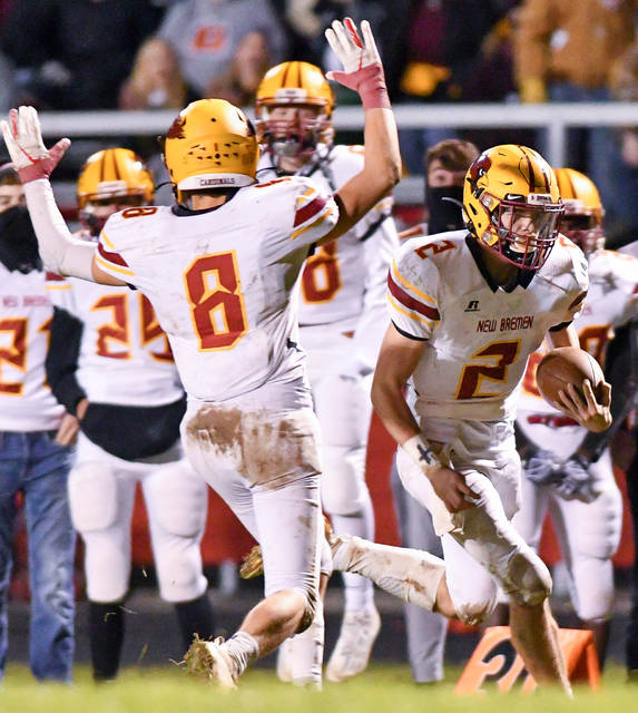 New Bremen's Mitchell Hays, right, runs while Branxton Krauss signals for a touchdown during a 43-yard TD run in the second quarter of a Division IV, Region 28 semifinal on Friday at Redskin Stadium in Fort Loramie.