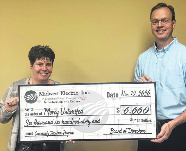 Midwest Electric CEO Matt Berry presents a $6,660 check to Bernadine Rohdes of Mercy Unlimited in Wapakoneta.