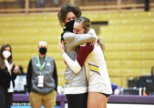New Bremen coach Diana Kramer, left, gives Josie Reinhart a hug after putting a state volleyball runner-up medal around Reinhart's neck following a 3-1 loss to Tiffin Calvert in the Division IV state championship match on Sunday at Vandalia-Butler's Student Activity Center.