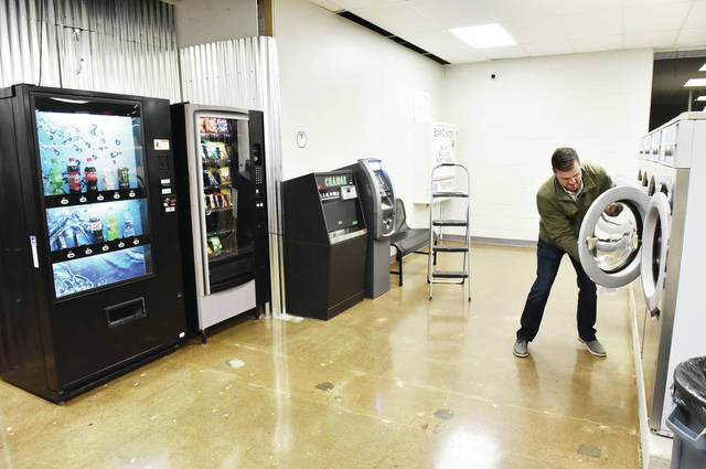Alex Adams, of Sidney, wipes down one of the new washers at his newly remodeled and upgraded business, Bubbles Laundromat, on Tuesday, Nov. 24. On the left are new pop and candy vending machines.