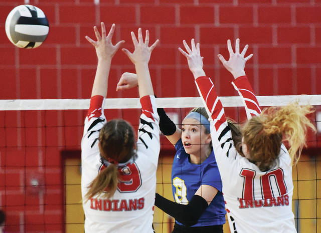 Russia's Cece Borchers spikes as Cedarville's Mili Smith, left, and Kyra Campbell try to block during a Division IV district final on Saturday at Troy's Trojan Activities Center.