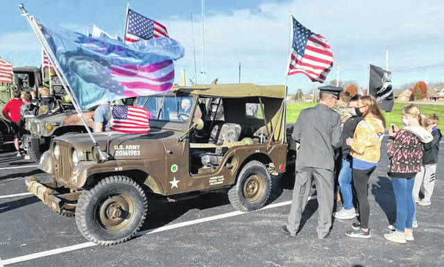 Russia native Joe Timmerman, who came as part of the cruise in component of Fort Loramie Schools Veterans Day program, talks with students about his Korean War era jeep that he owns.