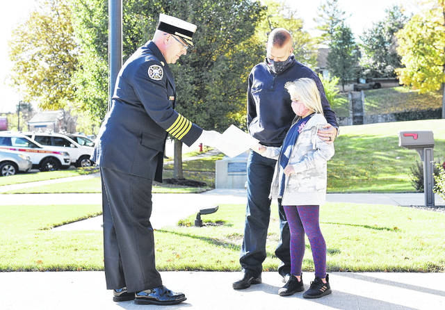 Retired Fire Chief Brad Jones, left, recognizes Brenna Davis, 8, the daughter of Deputy Fire Chief Dallas Davis (pictured in the center) and wife Bridget, on Oct. 16, with a letter of commendation for helping her father rescue a mother and daughter in distress on Stillwater River in August 2020.