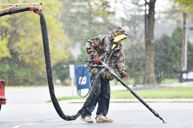 Superior Seal Coating employee Justin Barger, of Sidney, seals cracks with liquid tar in the parking lot of Sidney Tire on Sunday, Nov. 1, as snow falls around him.