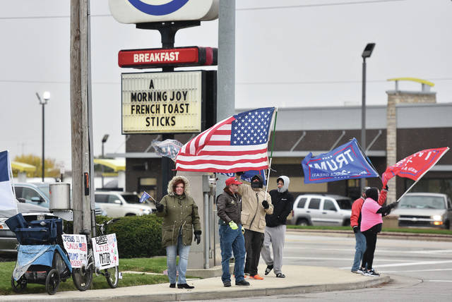 """A pro-Trump rally was held in front of Burger King on Sunday, Nov. 1. Signs attached to a bike said """"Jesus is my savior. Trump is my President and Babies lives matter."""" Participants were dressed warmly for the cold wind and light snow."""