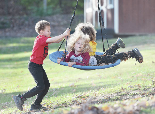Taylyn Henderson, left to right, 8, pushes his brothers Kacen Henderson, 3, and KJ Henderson, 6, all of Sidney, in a tire swing along Broadway Avenue on Sunday, Nov. 8. Watching nearby was their cousin Kallie Steward, 9, of Sidney, daughter of Darrick and Emily Steward, not pictured, who contented herself looking at leaves that had fallen on the ground. Unseasonably warm weather had many people playing outdoors. The three boys are the sons of Kenny Henderson, of Sidney.