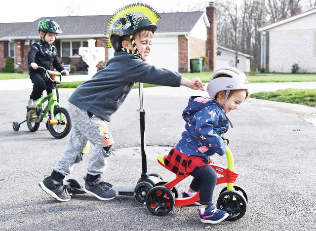 "Zander Lingerfelt, center, 4, chases his sister, Finley Lingerfelt, 1, near Arrowhead Drive on Friday, Nov. 13. Riding his bike behind them is their brother Ayden Lingerfelt, 5, all of Sidney, children of Casey and Sara Lingerfelt. Sara Lingerfelt said of why she brought her kids outside to play ""Won't be too many more sunny days. Winter's almost here."""