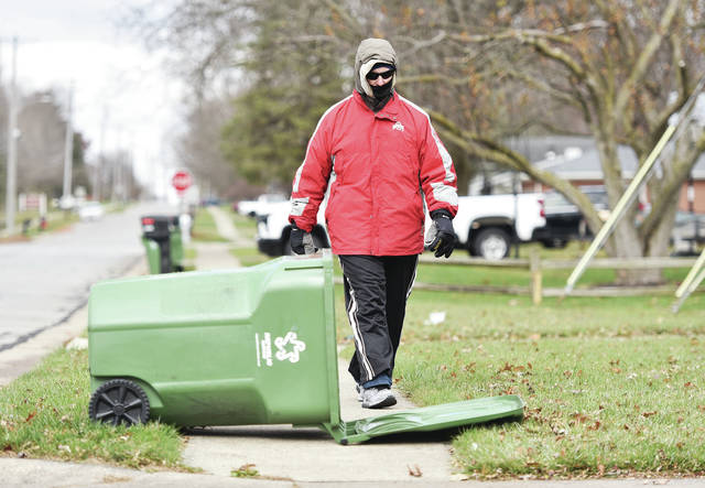 Dressed for the cold, Rick Denning, of Sidney, moves to avoid a fallen trash can as he takes his daily walk along Broadway Avenue on Tuesday, Nov. 17. Denning takes the walk daily to stay healthy.