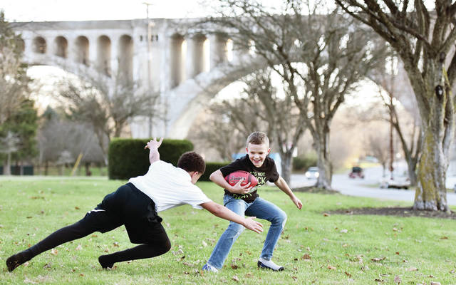 """Jace Herron, left, 12, son of Melissa Henry and Robert Herron, leaps towards Jonathan Davis, 10, both of Sidney, son of Ellean Davis and Jason Moore, during a game of three person football next to the Big Four Bridge on Thursday, Nov. 19. Jace said of the game """"We're just best friends trying to hang out."""" Also playing was Jonathan's brother, Christopher Davis, not pictured, 12."""