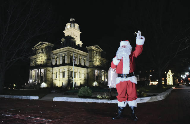 Santa waves from the courtsquare to cars that pass by on Wednesday, Nov. 18. Christmas music emanated from Santa as he walked from one corner of the square to the other ringing a bell.