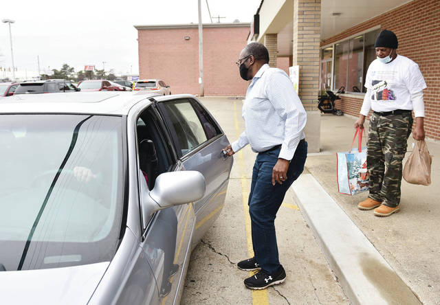 Dock Foy, of Tipp City, opens the door of a car driven by Christine Hughes, so that Mt. Zion Rev. Willie McGhee, both of Sidney, can put a turkey dinner in the back seat. Foy was handing out 20 free meals at his Wireless Doc Store on Tuesday, Nov. 24. Foy picked out people he knew could use the meal and sorted through requests on Facebook.