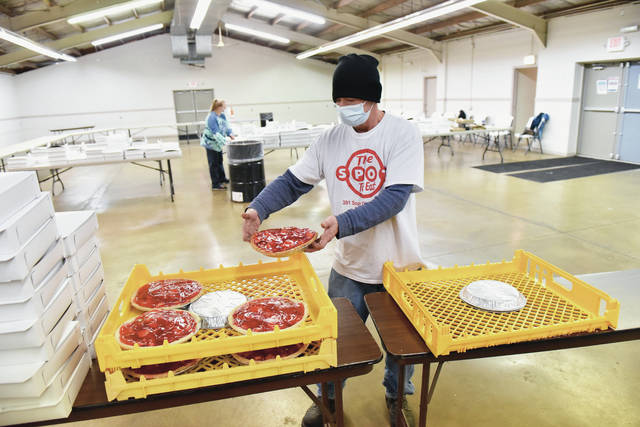 The Spot employee Fred Johnson, front, of Sidney, prepares fresh The Spot restaurant strawberry pies for boxing at the Shelby County Fairgrounds where around 1,000 pies were handed out on Wednesday, Nov. 25, to people who had ordered them for Thanksgiving. Behind Johnson is Tara Michael, of Sidney, organizing already boxed pies.