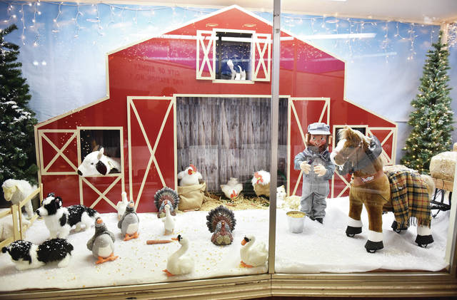A barn scene is one of the Christmas scenes that fill a window at Ron and Nita's this year. Store owner Juanita McCrum has made a tradition of decorating her display windows every year for Christmas. This year other displays include a manger scene, Sidney Fire Station No. 1 and an all white forest scene.