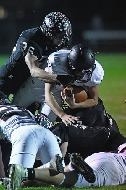 Minster quarterback Johnny Nixon is tackled by Covington's Connor Sindelier during a nonconference game on Thursday at Smith Field.