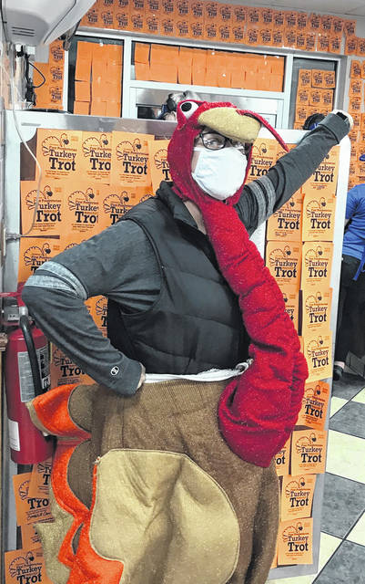 "The Turkey Trot mascot is surrounded by orange ""Turkey Bucks"" at Culver's in Sidney. The restaurant is once again partnering with First Presbyterian Church on the annual 5K race to raise money and food for Alpha Center,"