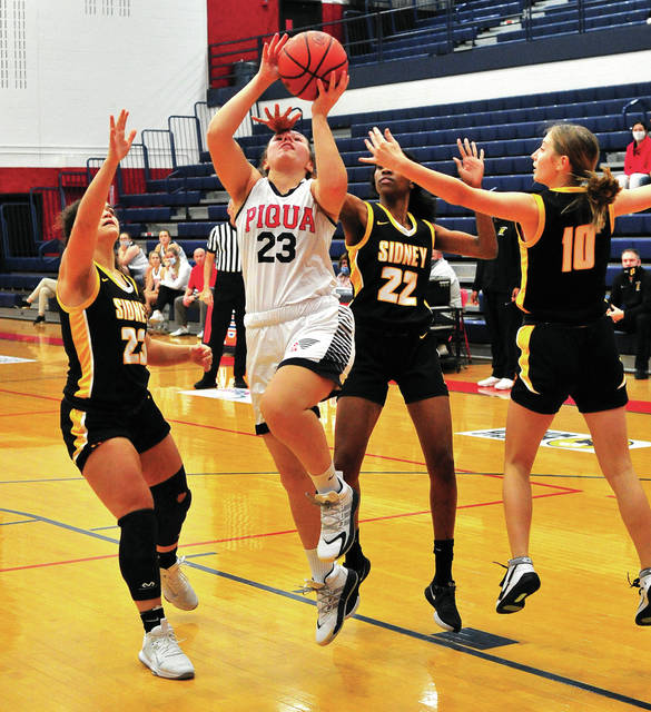 Piqua's Kenzie Anderson shoots with pressure from Sidney's Allie Stockton, left, Samantha Reynolds, middle right, and Peyton Wiley during a Miami Valley League game on Friday at Garbry Gymnasium in Piqua.