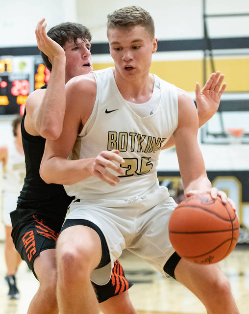 Botkins junior forward Jacob Pleiman dribbles with pressure from Minster's Justin Nixon during the first half of a nonconference game on Tuesday in Botkins. Pleiman, who was a second team all-Shelby County Athletic League selection last year, scored 31 points against the Wildcats.