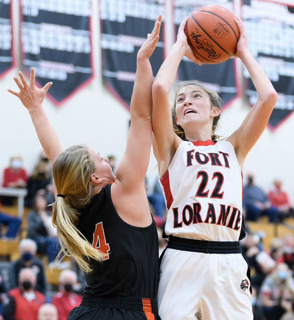 Fort Loramie senior forward Kenzie Hoelscher shoots over Minster's Ivy Wolf during the first half of a nonconference game on Saturday in Fort Loramie.