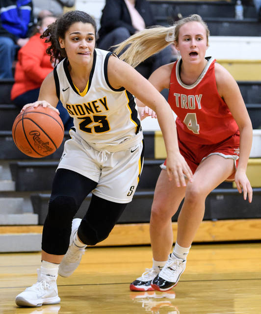 Sidney sophomore guard Allie Stockton dribbles with pressure from Troy's Madalynn Hughes during the first half of a Miami Valley League game on Friday in Sidney. Stockton led the Yellow Jackets with 20 points.