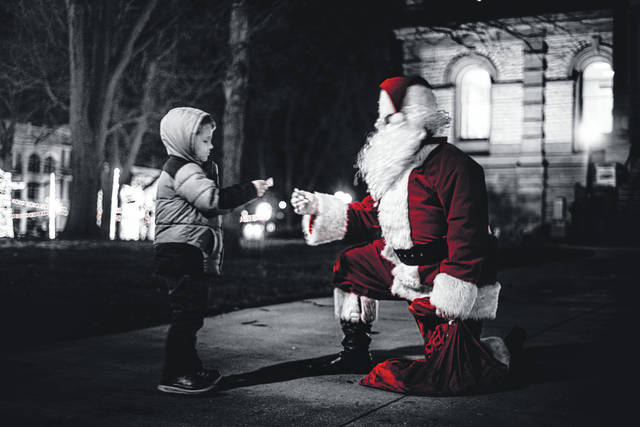 Santa Claus visits with a child during one of his trips to downtown Sidney.