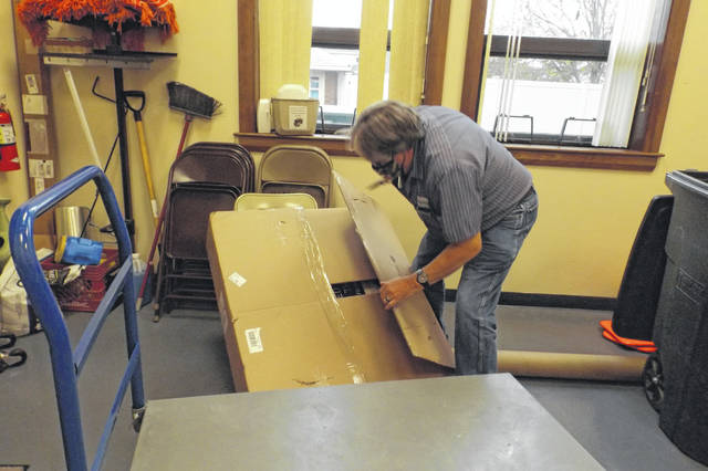 Rick Bice, maintenance supervisor at the courthouse, opens the sign for further inspection after its arrival.