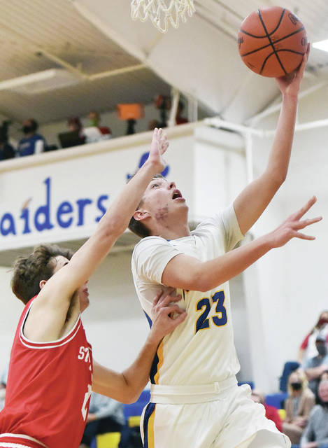 Russia's Jordan Meyer shoots with pressure from St. Henry's Bennett Gels during a nonconference game on Saturday at Clair C. Naveau Gymnasium in Russia.