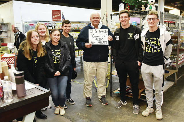 Agape Distribution Chief Executive Officer John Geissler, center, with Sidney High School Key Club members who stopped by Agape on Wednesday, Dec. 2, to pledge $1200 to the Agape food pantry.