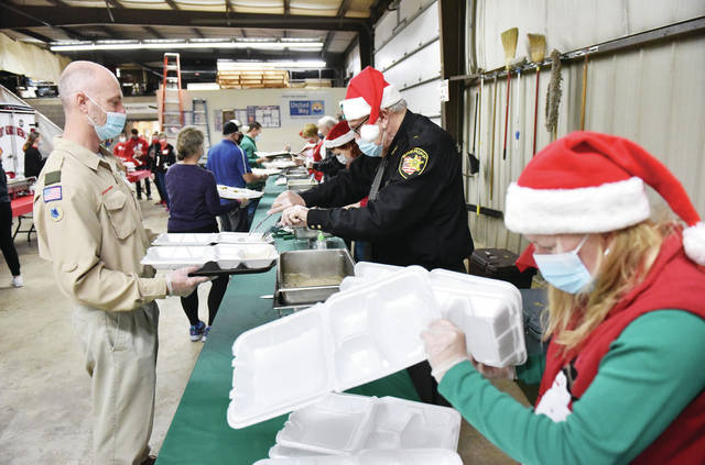 "Boy Scout Troop 95 Master Mark Bonifas, left to right, holds a food container up as Shelby County Sheriff John Lenhart scoops in slices of turkey as meals are prepared during the 39th Annual Community Christmas Dinner at the Shelby County Fairgrounds on Saturday, Dec. 5. Lenhart said of the dinner, ""I think especially this year this is appreciated and needed. I'm glad to do my part. Merry Christmas."" Arranging more food containers is Lenhart's daughter Rebecca Lenhart, of Jackson Center. Meals were handed out to cars as they drove past the Emergency Building on the fairgrounds. In the past people would go inside the building to eat their Christmas meals."