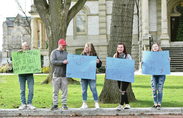 Family friends of a juvenile murder victim hold up signs asking for justice for the victim outside of the Shelby County Courthouse while the juvenile defendant in the murder case was inside attending their change of plea hearing on Friday, Dec. 11.