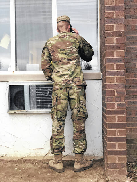 Spc. Nathan Miu stands outside the window of his grandfather Cloyd Miller, a veteran of the United States Navy, on Christmas Eve at Troy Rehabilitation & Healthcare Center. Miu, a member of the Army National Guard, surprised his family by returning home following a nine-month deployment to Kuwait. He first joined his family at church then went to Troy to see his grandpa.