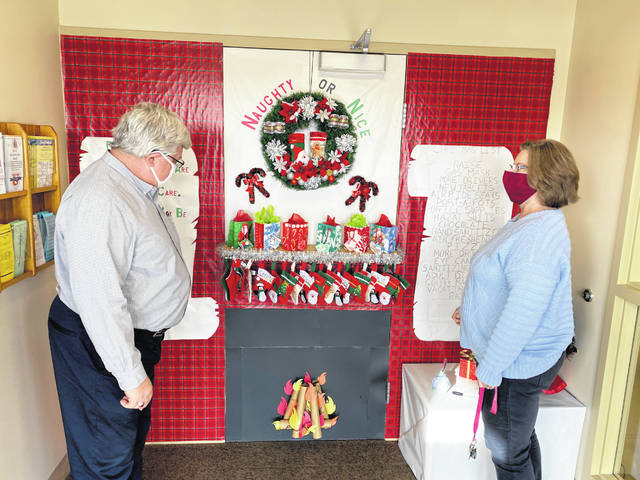 Transit Manager Ron Schalow listens intently as Dispatcher Becky Musser explains the details of the Transit Department's winning entry in the City of Sidney Christmas Door Decorating Contest.