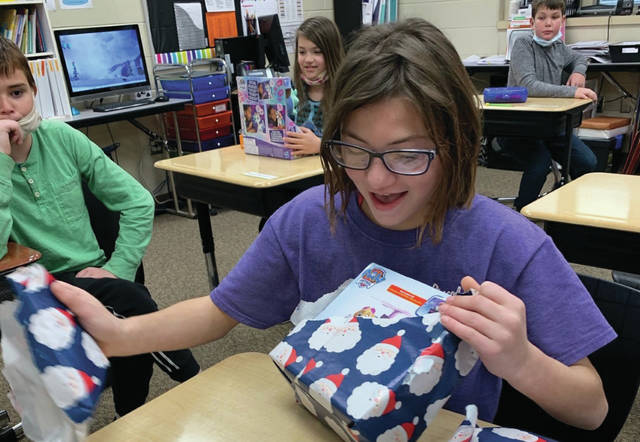 Jackson Center student Kendra Ordean opens her gifts from the Sidney Rotary Club.