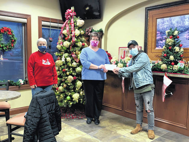 Pioneer's Senior Member Service Representative Deanna Wintrow, middle, presents a monetary donation to Fletcher United Methodist Church's God's Grocery representatives. This was just one of the six area food pantries that received donations from Pioneer employees.