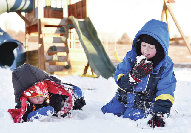 Bosten Shuster, right, 7, takes a lick of snow while playing with his brother, Greyson Shuster, 3, both of Fort Loramie, both the children of Hannah and Ryan Shuster. The brothers were playing in their neighbors yard, on Thursday, Dec. 3, because there was almost no snow to play with in their own on Woodland Drive.
