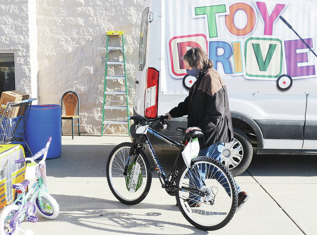 Paula Anderson, of Urbana, donates a bicycle to The Salvation Army Toy Drive in front of Walmart on Friday, Dec. 4. Anderson was donating the bike on behalf of Auria, an automotive parts manufacturer in Sidney. The toy drive lasted all day.