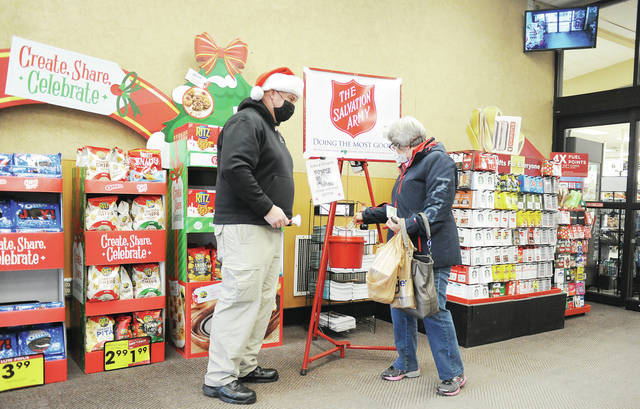 Sidney Police Chief Will Balling, left, rings The Salvation Army bell as Maria Perez, of Piqua, puts some money into his pot at Kroger on Saturday, Dec. 5.