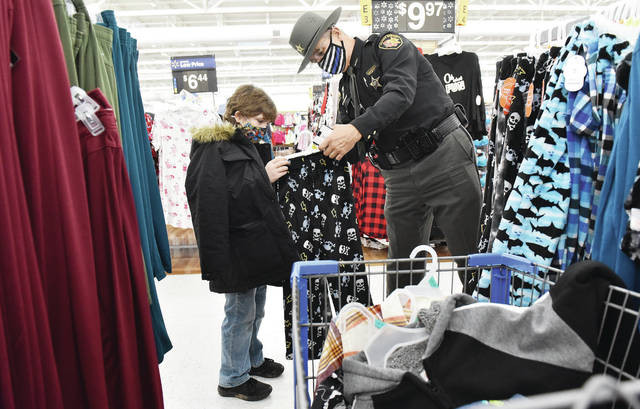 "Roger Moffitt, left, 10, of Sidney, son of Michelle Craun and Brad Moffitt, gets some help from Shelby County Sheriff Deputy Rod Austin in finding pajamas during the annual Shop with a Cop program at Walmart on Sunday, Dec. 6. This year kids were each given $200 to spend instead of the usual $150 due to successful fundraising. The kids had to spend $150 on clothes and then could spend the remaining $50 on toys. Officers from every village in Shelby County helped the kids spend their money. Also taking part were the Sidney Police Department and Ohio State Highway Patrol troopers. FOP 138 organizes the event. Guidance counselors were contacted in Shelby County schools to find kids for the program. This year Shop with a Cop was spearheaded by Shelby County Sheriff's Deputy Bill Booth who said, ""I want to thank everyone who donated."""