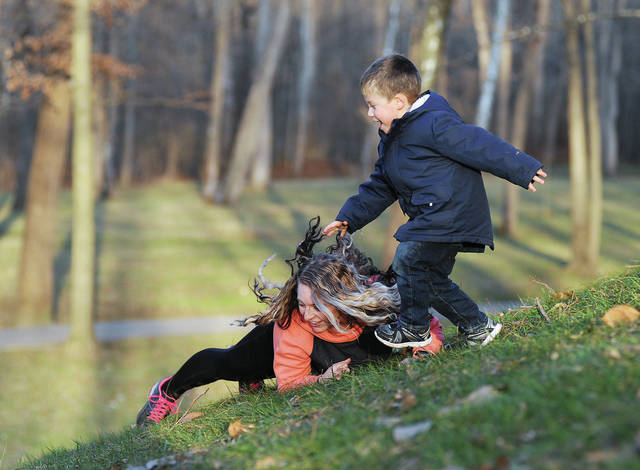 """Denielle Thornton, left, rolls down a hill at Tawawa Park in a race with her son Jason Hytinen, 4, both of Sidney, on Thursday, Dec. 10. The two were taking advantage of warm weather in the lower 50's. Thornton said, """"We normally come here all the time."""" Jason is also the son of Nate Hytinen."""