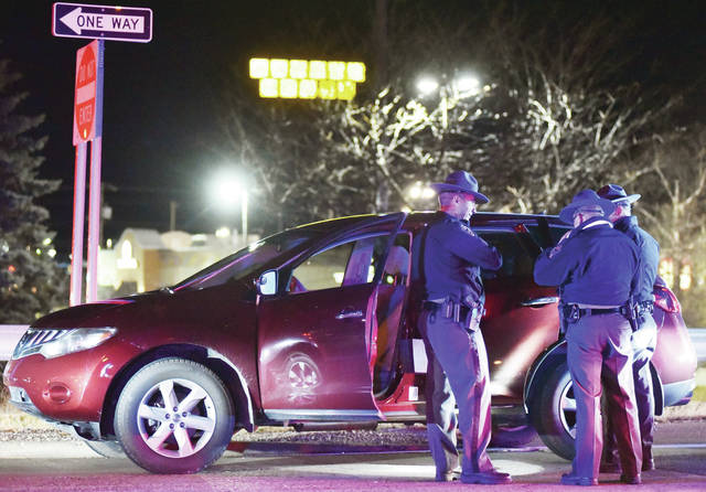 Ohio State Highway Patrol officers investigate a SUV that was involved in a chase on Interstate 75 that ended in Sidney at around 11:15 p.m. on Sunday, Dec. 13. The chase began at the rest area north of Wapakoneta near mile marker 114 on I-75 where an Ohio State Highway Patrol officer from the Wapakoneta Post attempted to pull over the SUV for going 85 mph.