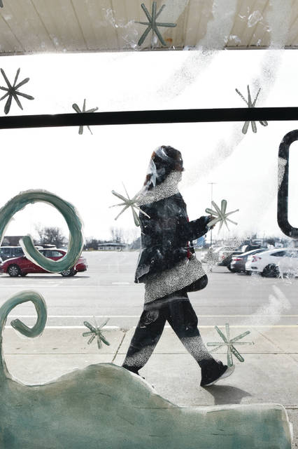 Kim Sabroff, of Sidney, walks past a door to Hong Kong Buffet and Grill decorated with falling and blowing snow on Tuesday, Dec. 15. The weather should more closely match the window decorations on Wednesday, Dec. 16, when snow is in the forecast. The Hong Kong Buffet and Grill has remained open and still offers indoor dining and takeout.