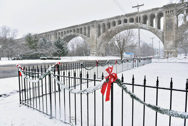 Red ribbons decorating a fence give some color to an almost black and white view of the Big Four Bridge as snow falls on Wednesday, Dec. 16.