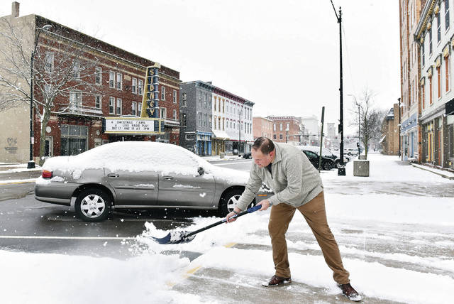The Bridge Manager Doug Smith, of Sidney, shovels the sidewalk in front of The Bridge as snow continues to fall Wednesday morning, Dec. 16.