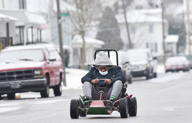Anthony Snowden, 15, of Sidney, son of Tameka Johnson, zips down Jefferson Street as he tries out the go-kart he had just acquired on Thursday, Dec. 17.