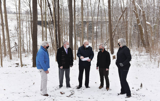 Sidney Mayor Mike Barhorst, center, discusses the Ohio Capital Budget Grant received by the City of Sidney with, left to right, Parks and Recreation Director Duane Gaier, Shelby County Commissioner Tony Bornhorst, Great Miami Riverway Director Dan Foley and Sidney Parks and Recreation Board Chair Amy Zorn along the site of the future trail. The trail will pass from the east side of Interstate 75 under the bridge in the background along the river and along the route of the former Miami & Erie Canal to Kuther Road.